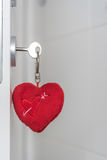 Heart shaped pendant. Heart shaped plush pendant on key in lock of white door royalty free stock images