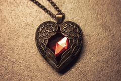Heart shaped pendant. With red diamond and wings embracing the heart. Copper colored royalty free stock images