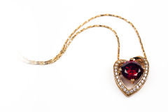 Heart shaped pendant with red stone Royalty Free Stock Photos