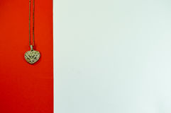 Heart-shaped pendant. On a red strip on a white background stock photo