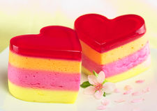 Heart-Shaped Peruvian Cake Called Torta Helada. Colorful Peruvian heart-shaped jelly-pudding cakes called Torta Helada with a peach blossom on the plate ( Royalty Free Stock Photo