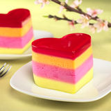 Heart-Shaped Peruvian Cake Called Torta Helada. Colorful Peruvian heart-shaped jelly-pudding cakes called Torta Helada with a blooming peach branch in the back ( Royalty Free Stock Photos