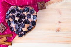 Pie in the shape of a heart of cherries on a wooden background and beside a cloth royalty free stock images