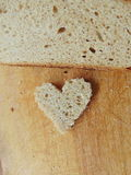 Heart shaped piece of bread in front of full bread Stock Photos