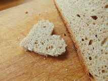 Heart shaped piece of bread in front of full bread Royalty Free Stock Photo