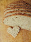 Heart shaped piece of bread in front of full bread Royalty Free Stock Photography