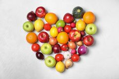 Heart shaped pile of fruits and vegetables on light background. Flat lay stock images