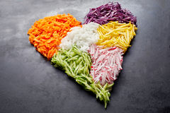 Heart-shaped pile of grated vegetables. As ingredients for cooking placed over black surface background. Healthy organic food concept, close-up studio shot from Royalty Free Stock Photos