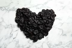Heart shaped pile of sweet dried plums on marble background, top view. Healthy fruit royalty free stock photography