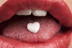 Heart shaped pill in woman's mouth Stock Image