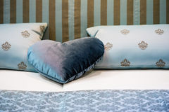 Heart shaped pillow on the bed in the bedroom. Blue heart shaped pillow on the bed in the bedroom Royalty Free Stock Photography