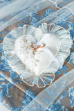 Heart-shaped pillow with chiffon lace and wedding gold rings Stock Photo