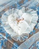 Heart-shaped pillow with wedding gold rings Royalty Free Stock Images