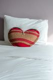 Heart shaped pillow on white bed and white pillow. Royalty Free Stock Image