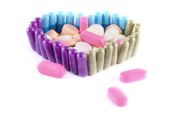HEART SHAPED PILLS WITH ASSORTED CAPSULES AND TABL. Pills shaped together in the form of a heart with assorted capsule and tablets inside on white background royalty free stock image