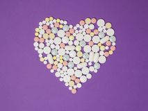 Heart-shaped pills on solid purple background. Your personal health. Using tablets. cure, medicine, pills, vitamin. Medical help. Doctor`s help. Health care Stock Images