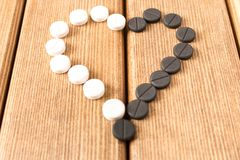 Heart-shaped pills on a wooden table . Heart-shaped pills on a wooden table Royalty Free Stock Images