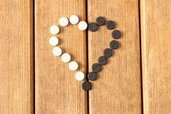 Heart-shaped pills on a wooden table . Heart-shaped pills on a wooden table Royalty Free Stock Photos