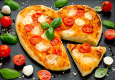 Heart-shaped pizza with cherry tomatoes, mozzarella and basil on Stock Images