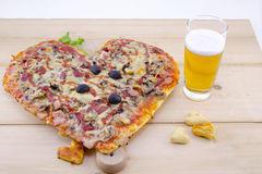 Heart shaped pizza and a glass of beer Stock Photography