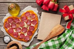 Heart shaped pizza. With pepperoni and mozzarella. Valentines day greeting card. Top view with space for your text stock image