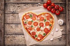Heart shaped pizza margherita love food symbol with mozzarella, tomatoes, parsley, and garlic composition on cutting. Board, vintage wooden table background stock images
