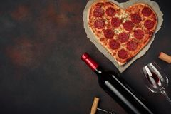 Heart shaped pizza with mozzarella, sausagered with a bottle of wine and wineglas on rusty background. Heart shaped pizza with mozzarella, sausagered with a stock images