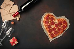 Heart shaped pizza with mozzarella, sausagered, wine bottle, two wineglass, gift box on rusty background. Top view