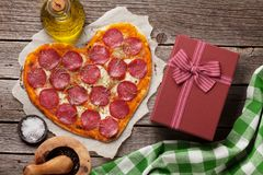 Heart shaped pizza. With pepperoni and mozzarella and gift box. Valentines day greeting card Royalty Free Stock Photos