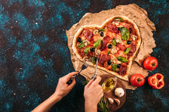 Heart shaped pizza with tomatoes and prosciutto for Valentines Day with eating hands. Food concept of romantic love Royalty Free Stock Photo