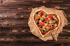 Heart shaped pizza with tomatoes and prosciutto for Valentines Day on vintage wooden background. Food concept of Royalty Free Stock Image