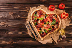 Heart shaped pizza with tomatoes and prosciutto for Valentines Day on vintage wooden background. Food concept of Royalty Free Stock Photos