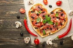 Heart-shaped pizza, Valentine`s Day. With vegetables. A concept of tasty and healthy food with love. Free-lay.  royalty free stock photos