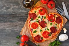 Heart shaped pizza for Valentines Day over rustic wood, top view table scene with ingredients. Heart shaped pizza for Valentines Day over a rustic wood royalty free stock photo