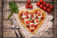 Heart shaped pizza for Valentines day with. Pepperoni, mozzarella, tomatoes, parsley and garlic on vintage wooden table background. Food symbol of romantic love Royalty Free Stock Photos
