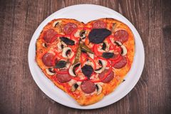 Heart shaped pizza on white plate Stock Image