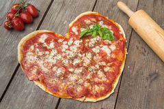 Heart-shaped pizza. On wood with tomatoes and rolling pin Royalty Free Stock Photo
