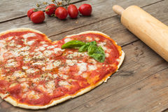 Heart-shaped pizza. On wood with tomatoes and rolling pin stock photography