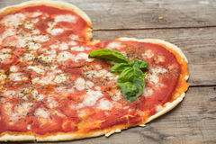 Heart-shaped pizza. On wood with tomatoes and rolling pin Stock Photos