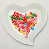 Heart shaped plate and colored candy Stock Photography