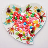 Heart shaped plate and colored candy Stock Images