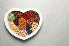 Heart shaped plate with different dried fruits and nuts. Space for text. Heart shaped plate with different dried fruits and nuts on table. Space for text stock images