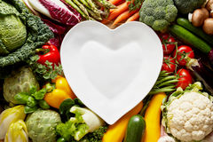 Heart-shaped plate over vegetables Stock Photos