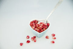Heart-shaped, plate,, pomegranate fruit,  spoon Royalty Free Stock Images