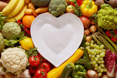 Heart shaped plate among vegetables. Empty white heart shaped plate in the middle of full frame shot among fresh colorful vegetables and fruits surrounding it Stock Image
