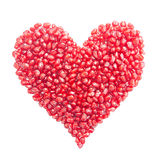 Heart-shaped pomegranate seeds isolated on white Stock Images