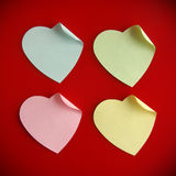 Heart shaped post it. Background of four heart-shaped colorful post its over red royalty free stock photos