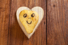 Heart shaped potato with happy face on wood, copy space Stock Image