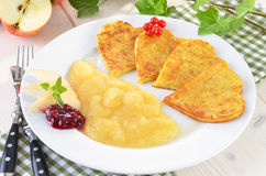 Heart-shaped potato pancakes. Baked potato pancakes in the shape of a heart with applesauce, cranberries and redcurrants Royalty Free Stock Photo