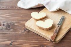 Heart shaped potato on the plank Royalty Free Stock Photos